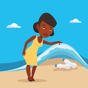 海の波の下でペットボトルを示す女性。