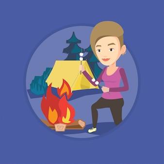 Женщина жарит зефир над костром.