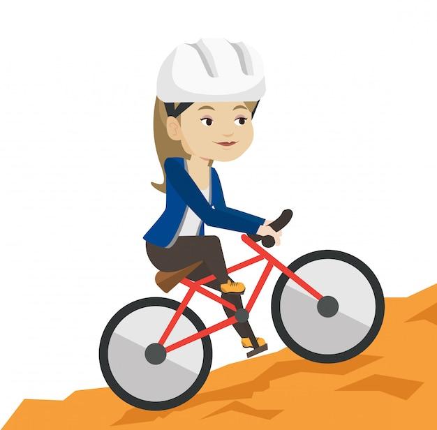 Молодая женщина на велосипеде путешествуя в горах