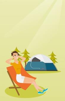 キャンプで折りたたみ椅子に座っている女性。
