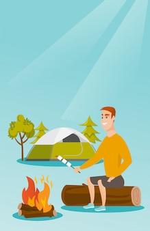 白人男がキャンプファイヤーでマシュマロを焙煎します。