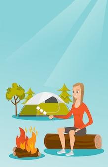 白人の女の子はキャンプファイヤーの上にマシュマロを焙煎します。