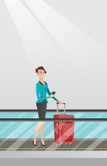 女性が空港でエスカレーターでスマートフォンを使用して