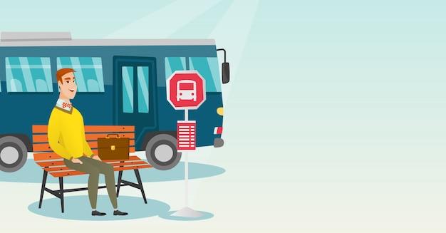 Кавказский человек ждет автобус на автобусной остановке.