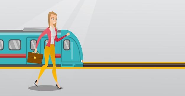 鉄道駅のプラットフォームの上を歩く若い女性。