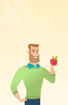 Молодой человек держит яблоко