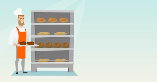 Счастливый молодой пекарь, держа поднос с хлебом.