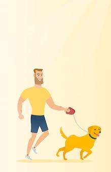 若い男が彼の犬を連れて歩いています。