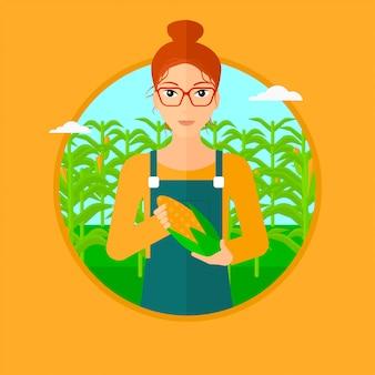 Фермер держит кукурузу.