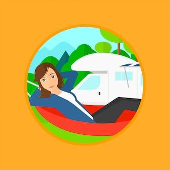 Женщина лежа в гамаке перед домом на колесах.