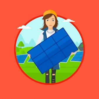 太陽電池パネルを保持している女性。