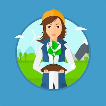 ペットボトルで成長している植物を保持している女性。