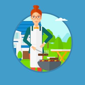 バーベキューグリルで肉を料理する女性。