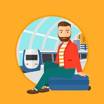 Человек сидит на чемодане на вокзале.