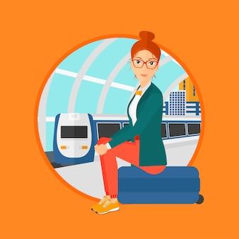 Женщина сидит на чемодане на вокзале.