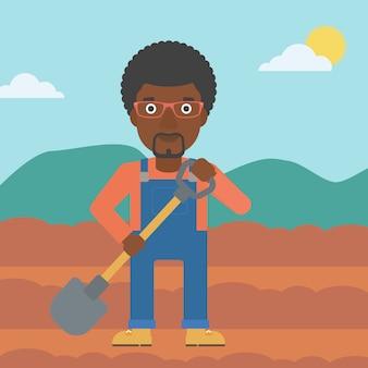 シャベルでフィールド上の農家