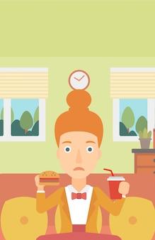 ハンバーガーを食べる女性。