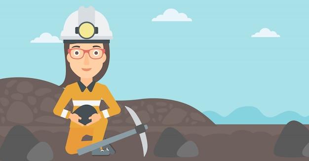 鉱山労働者が手で石炭を持っています。