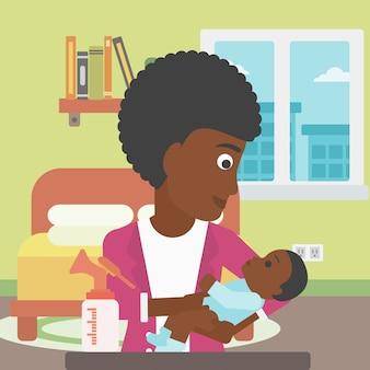 赤ちゃんと搾乳器を持つ母親。