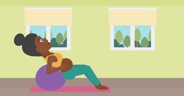 体操のボールに妊娠中の女性。