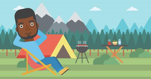 キャンプで折りたたみ椅子に坐っていた男。