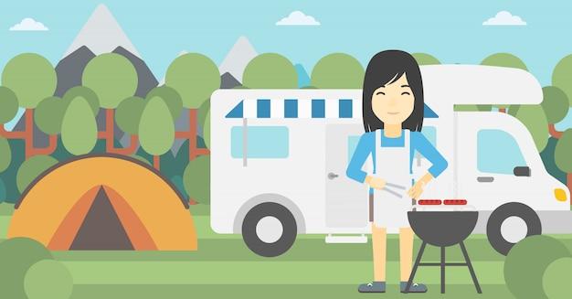 Женщина, имеющая барбекю перед жилым фургоном.
