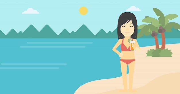 ビーチでカクテルを持つ女性。