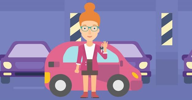 新しい車からのキーを保持している女性。