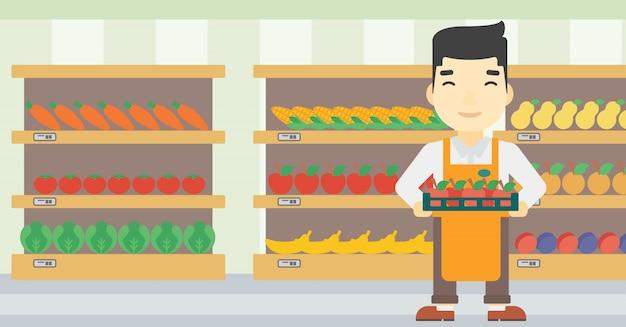 りんごがいっぱい入った箱でスーパーマーケットワーカー。