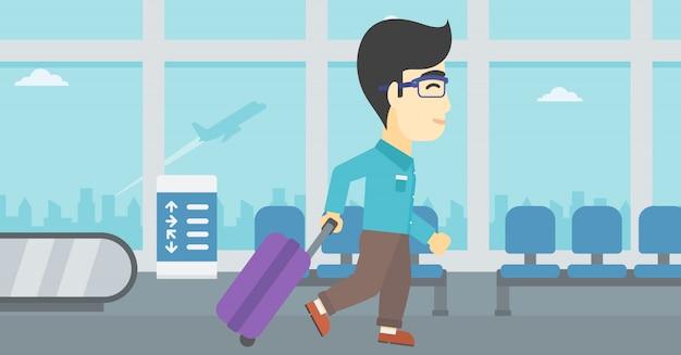 Человек идет с чемоданом в аэропорту.