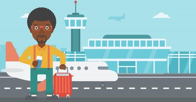 スーツケースと空港でのチケットを持つ男。