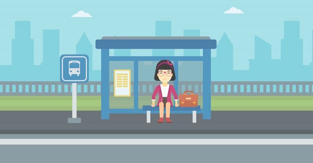 Женщина ждет автобуса на автобусной остановке.