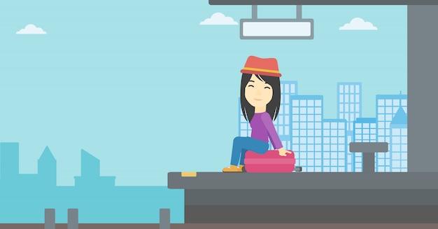 駅でスーツケースの上に座っている女性。