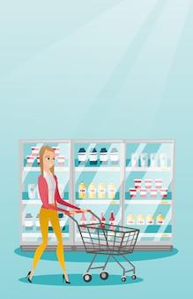 スーパーマーケットのトロリーを持つ若い白人女性。