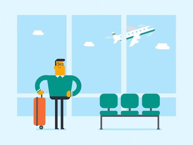 Кавказский человек, стоящий в аэропорту с чемоданом.