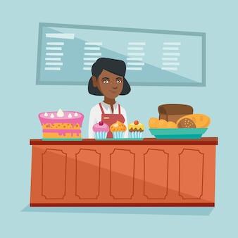 パン屋のカウンターの後ろに立っている労働者。