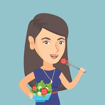 Кавказская женщина ест здоровую овощной салат.