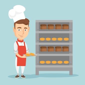 Счастливый молодой мужской пекарь держит поднос хлеба.