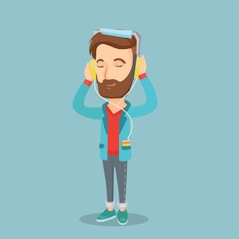 Молодой человек в наушниках слушает музыку.