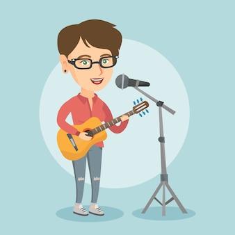 女性はマイクに向かって歌い、ギターを弾きます。