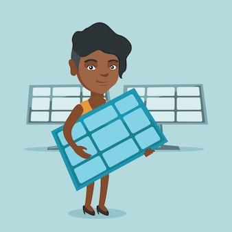 太陽電池パネルを保持している若いアフリカ系アメリカ人女性。