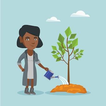 若いアフリカ系アメリカ人の女性が木に水をまきます。