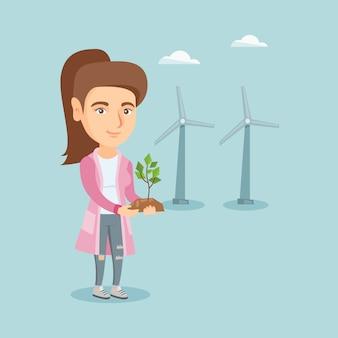 小さな植物を保持している風力発電所の白人労働者。