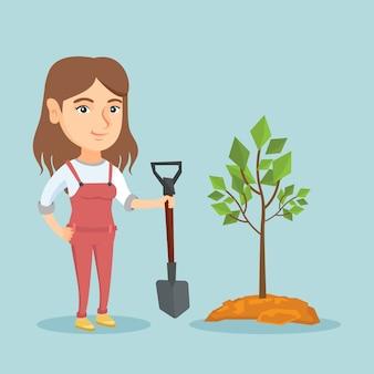 若い白人女性が木を植えます。