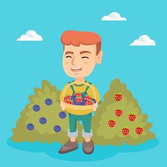 イチゴとブルーベリーのバスケットを持つ少年。