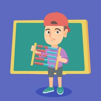 緑の黒板とそろばんを持つ少年。