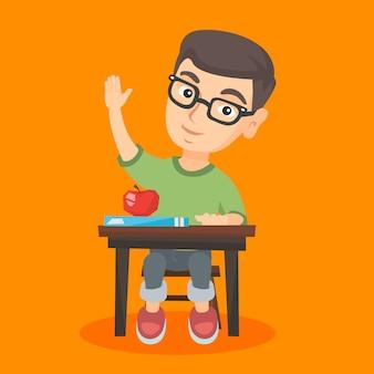Школьник, сидя за столом с поднятой рукой.