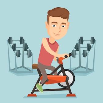 若い男が静止した自転車に乗る。