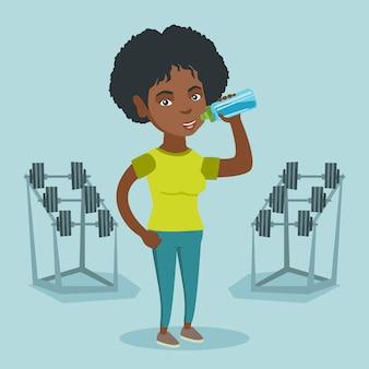 若いアフリカ系アメリカ人のスポーツウーマン飲料水。