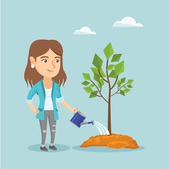 若い白人女性が木に水をまきます。